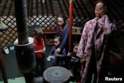 FILE - The wife and children of Setevdorj Myagmartsogt gather around their new coal burning stove while talking to reporters in their tent-like ger home in Ulaanbaatar, Mongolia, Jan. 29, 2017.
