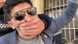 Polis gənc fəalı aksiya zamanı ağzını əli ilə bağlayır