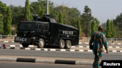FILE - A man walks across the road toward a police water cannon truck following a government security alert in Abuja, Nigeria, Dec. 8, 2015.