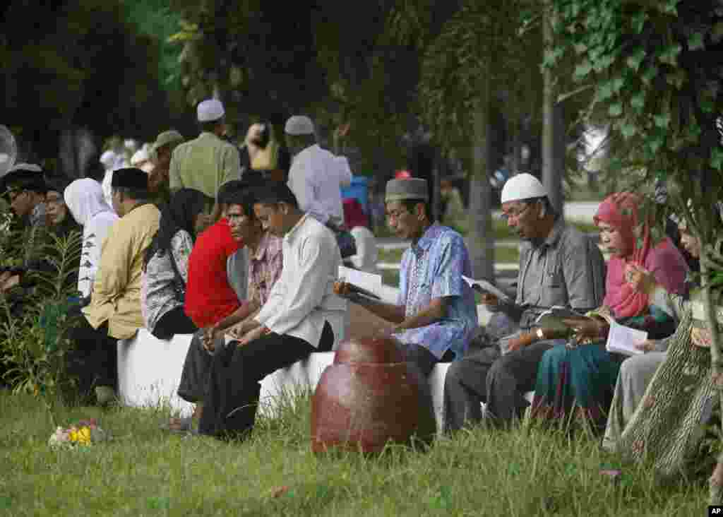 Acehnese read the Quran at a mass grave during the 10th anniversary of the tsunami in Siron, Aceh Besar, Indonesia, Friday, Dec 26, 2014.
