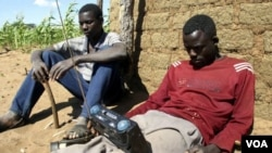 FILE - Zimbabweans listen to a radio for an announcement of election results in Umguza.