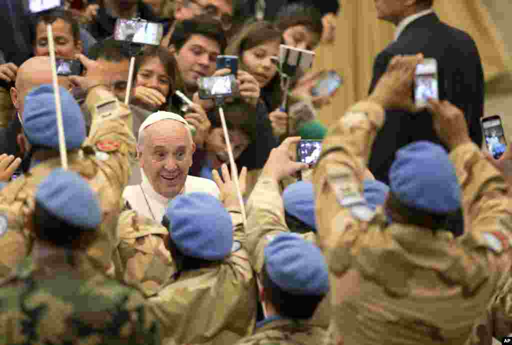 Pope Francis is greeted by Argentinian officers of the United Nations Peacekeeping Force in Cyprus, UNFICYP, as he arrives for his weekly general audience in Pope Paul II hall, at the Vatican.