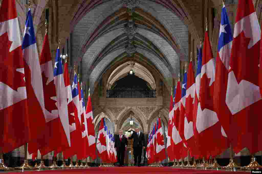 Canada's Prime Minister Stephen Harper (R) walks in the Hall of Honor with Chile's President Sebastian Pinera on Parliament Hill in Ottawa.