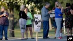 """FILE - Voters stand in line to vote at an early voting polling site in San Antonio, Texas, on Oct. 20, 2014. The U.S. Supreme Court will hear arguments Tuesday in a """"one person, one vote"""" case stemming from Texas."""