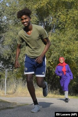 Mowlid Nur, left, and Ubah Yusuf go for a run during an Athletics United event in Logan, Utah