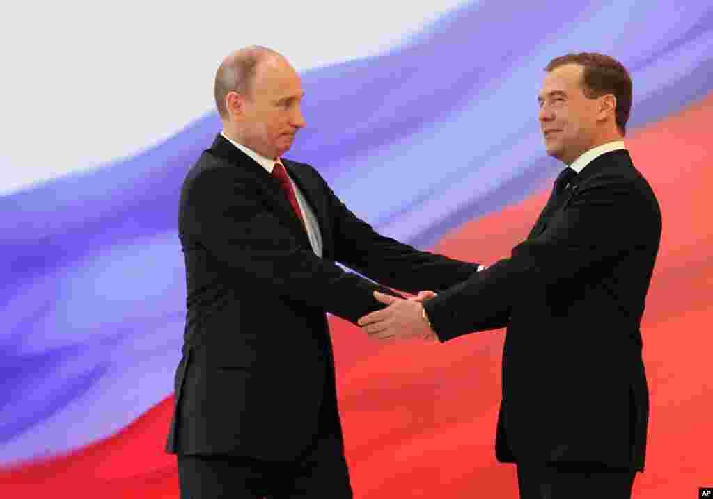 Presiden Rusia Vladimir Putin (kiri) dan mantan Presiden Dmitry Medvedev berjabat tangan pada upacara pelantikan.