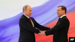 Russian President Vladimir Putin, left, and former President Dmitry Medvedev shakes hands at the inauguration ceremony.