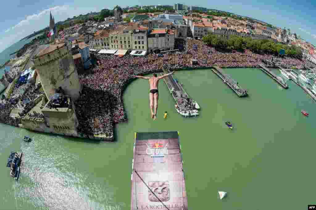 ក្នុងរូបថតដែលផ្តល់ដោយក្រុមហ៊ុនគោជល់ (Red Bull) បង្ហាញពីកីឡាកររុស៊្សី Artem Silchenko លោតពីលើអគារ Saint Nicolas កំពស់ ២៧,៥ ម៉ែត្រ ក្នុងកម្មវិធីប្រកួតលំដាប់ពិភពលោក Red Bull Cliff Diving នៅក្នុងទីក្រុង La Rochelle ប្រទេសបារាំង។