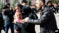A Turkish man helps a Syrian woman carrying a wounded Syrian girl to a hospital in Kilis, Turkey, Feb. 15, 2016.