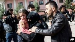 Người đàn ông Thổ Nhĩ Kỳ giúp một phụ nữ Syria ẵm bé gái bị thương tới bệnh viện ở Kilis, Thổ Nhĩ Kỳ, ngày 15/2/2016.