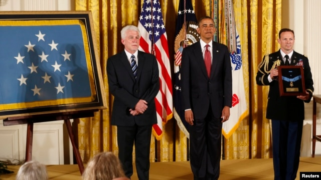 US President Barack Obama during a ceremony to present Medal of Honor posthumously to Ray Kapaun (L), the nephew of U.S. Army Chaplain (Captain) Emil Kapaun, April 11, 2013