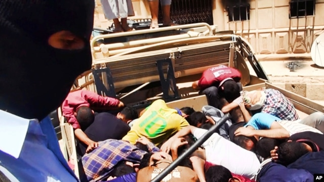 An Islamic fighter guards alleged Iraqi soldiers lying in a truck bed in this photo posted on a militant website June 14, 2014.