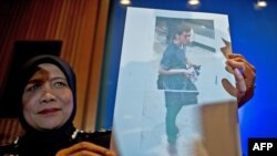 A Malaysian police official displays a photograph of 19-year-old Iranian Pouria Nour Mohammad Mehrdad, one of the two men who boarded missing Malaysia Airlines MH370 flight using stolen European passports to the media at a press conference near Kuala Lumpur International Airport in Sepang on March 11, 2014.