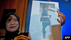 A Malaysian police official displays a photograph of 19-year-old Iranian Pouri Nourmohammadi, one of the two men who boarded missing Malaysia Airlines MH370 flight using stolen European passports to the media at a press conference near Kuala Lump