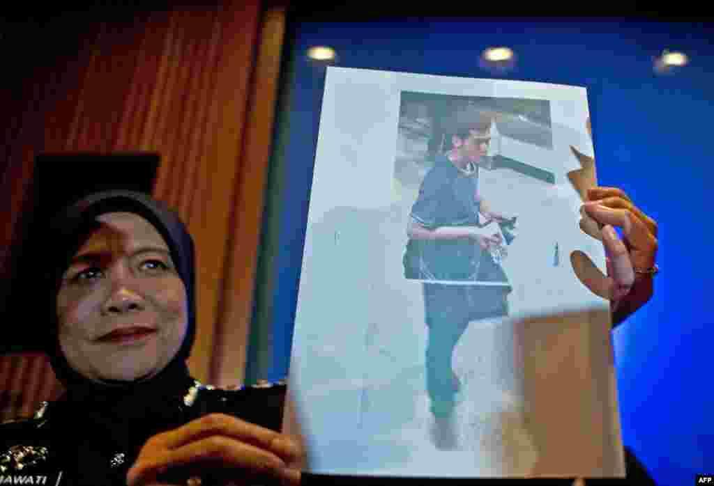 Uma agente da polícia malaica mostra uma fotografia do iraniano de 19 anos, Pouria Nour Mohammad Mehrdad, um dos dois passageiros que embarcaram no avião desaparecido, usando passaportes europeus roubados