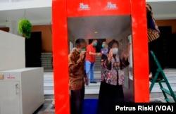 Wali Kota Surabaya Tri Rismaharini mencoba bilik sterilisasi tipe tunnel buatan ITTS yang dipasang di sekitar Balai Kota (Foto: VOA/ Petrus Riski)