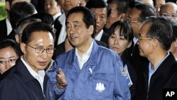 日本首相菅直人(中)和南韓總統李明博(左)中國總理溫家寶在訪問福島的撤離中心時交談