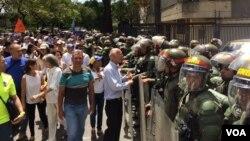 Manifestantes se detienen frente a la Guardia Nacional Bolivariana (GNB) en Caracas, para mostrar su descontento. 1 de abril de 2017. Foto: Álvaro Algarra / VOA.