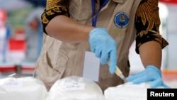 Seorang petugas Badan Narkotika Nasional (BNN) sedang menyiap paket-paket metamfetamin atau sabu-sabu yang akan dimusnahkan di Jakarta, 4 Mei 2018. BNN Sulawesi Tengah menengarai sebuah kelurahan di Kota Palu sebagai pusat transaksi narkoba beromzet miliaran rupiah per bulan.