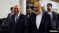 Sartaj Aziz, left, adviser to Pakistan's prime minister on foreign affairs, escorts Iranian Foreign Minister Javad Zarif to their meeting at the Foreign Ministry in Islamabad, April 8, 2015.