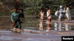 Nạn nhân lũ lụt lội qua 1 cánh đồng ngập nước sau trận mưa lớn ở Jhang, tỉnh Punjab, 11/9/2014.