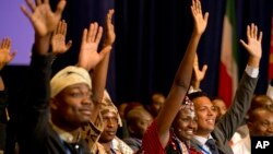 Josephine Kolea of Kenya (2nd R) raises her hand to ask a question of President Barack Obama with other attendees of the Summit of the Washington Fellowship for Young African Leaders during Obama's town hall, July 28, 2014, in Washington.