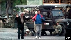 FILE - Local residents walk with their hands raised as Uzbek soldiers take positions to disperse protesters in Andijan, Uzbekistan, May 13, 2005.