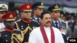 Presiden Mahinda Rajapaksa (depan)menyaksikan parade militer di Colombo (27/5). Pemerintahan Sri Lanka menghadapi tuduhan pelanggaran HAM di akhir perang saudara dengan pemberontak Tamil.