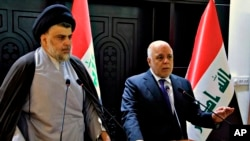 FILE - In this photo provided by the Iraqi government, Iraqi Prime Minister Haider al-Abadi, right, and Shiite cleric Muqtada al-Sadr hold a press conference in Baghdad, Iraq, May 20, 2018.