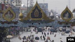Warga Thailand berjuang di tengah genangan banjir di distrik Rangsit, pinggiran kota Bangkok (21/10).