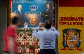 Tourists walk past a souvenir store with a sign featuring the image of Spain's King Juan Carlos and Crown Prince Felipe in central Madrid, Spain, June 17, 2014.