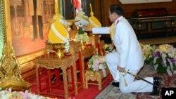 ထိုင္းအာဏာသိမ္း စစ္ေခါင္းေဆာင္ ဗိုလ္ခ်ဳပ္ Prayuth Chan-ocha ထုိင္းဘုရင့္ပန္းခ်ီကားခ်ပ္ေရွ႕မွာ စစ္ေကာင္စီအႀကီးအကဲရာထူးကို ေထာက္ခံမႈ ရယူစဥ္။