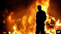 英國警方從星期五開始在倫敦5個區實施三十天的抗議遊行禁令。圖為上個月發生暴亂和嚴重襲警事件﹐街上的汽車遭燒燬。