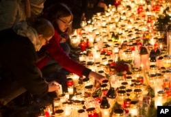 FILE - Candles are placed outside the French embassy in Vilnius, Lithuania, for the victims in Friday's attacks in Paris, Nov. 14, 2015.