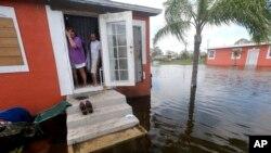 ທ້າວ Quintana ແລະນາງ Liz Perez ພາກັນເບິ່ງນ້ຳຖ້ວມ ຂ້າງນອກບ້ານຂອງພວກເຂົາເຈົ້າ ຫຼັງຈາກທີ່ ເຣີຣິເຄນ Irma ໄດ້ເຂົ້າປະທະຂົງເຂດ, 11 ກັນຍາ, 2017, ໃນເມືອງ Immokalee, Florida.