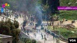 Gambar yang disiarkan oleh TV pemerintah menunjukkan bentrokan antara pasukan keamanan dan demonstran di kota Daraa, Jumat (8/4).