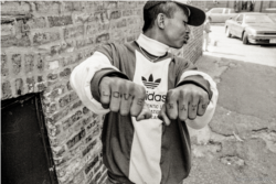 Another Cambodian Ricky shows the tattoos on his hands in a back alley of an apartment complex in Uptown, Chicago.