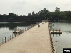 A small group of tourists walk on a bridge connecting to the Angkor Wat temple in Siem Reap province, Cambodia, March 18, 2020. (Hul Reaksmey/VOA Khmer)
