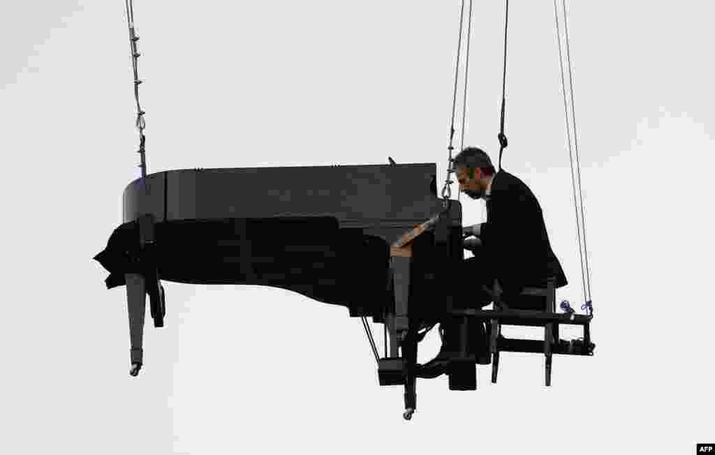 "Brazilian pianist Ricardo de Castro Monteiro performs in the air at a piano hanging from wires, during the annual ""Virada Cultural"" event, in Sao Paulo, Brazil, June 21, 2015."
