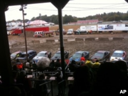 Junkers line up, rear ends facing the arena, before the start of a demo derby event at a county fair.