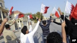 Anti-government protesters holding Bahraini flags walk in front of riot police during a protest held by al-Wefaq in Manama, January 7, 2012.