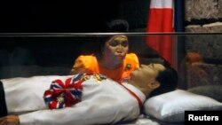 In this file photo, former Philippine first lady Imelda Marcos kisses the glass coffin of her husband, late dictator Ferdinand Marcos, when his body was on display in Ilocos Norte province, on March 26, 2010.