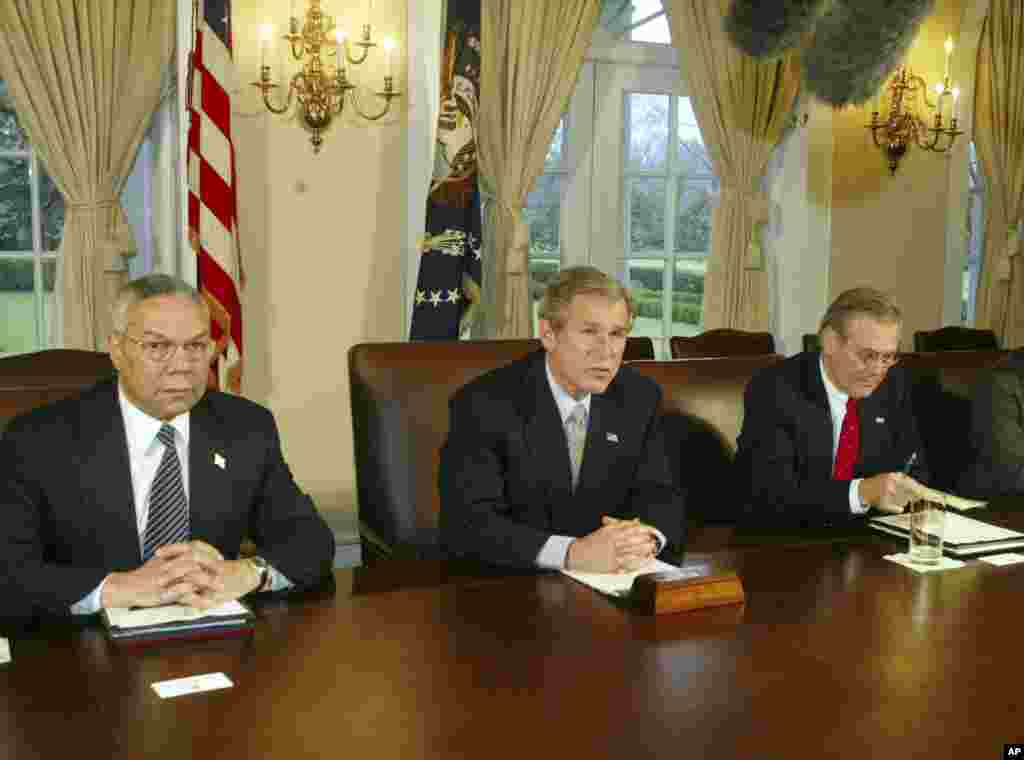 Then President George W. Bush makes a statement to reporters while Secretary of State Colin Powell and Secretary of Defense Donald Rumsfeld look on following a Cabinet meeting, March 20, 2003.