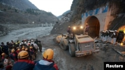 Members of Indo-Tibetan Border Police (ITBP) watch as a machine is used to clear a tunnel