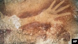 Gambar stensil tangan di gua di Sulawesi, yang menurut studi baru sama tuanya dengan seni prasejarah di Eropa. (AP/Kinez Riza, Nature Magazine)
