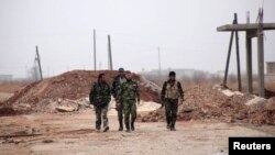 Forces loyal to Syria President Bashar al-Assad walk in the town of Tel Arn in Aleppo after capturing it from rebels Nov. 12, 2013.