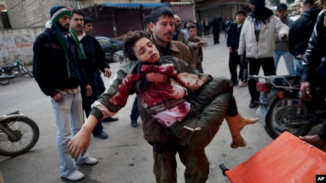 In this March 11, 2012 photo, a man carries a boy who was severely wounded during heavy fighting between Syrian rebels and Syrian Army forces in Idlib, north Syria.
