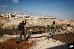 FILE - Workers carry material at a construction site in the West Bank settlement of Maaleh Adumim, Jan. 22, 2017.