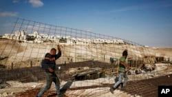 Des travailleurs transportent du matériel sur un chantier de construction dans la colonie de Maaleh Adumim, en Cisjordanie, 22 janvier 2017.
