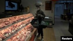 一名戴著口罩的互聯網供貨商在北京亦莊一家肉店為網上訂戶購買豬肉。(2020年2月8日)